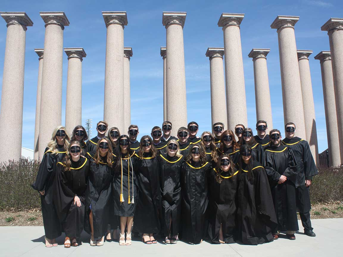 students in black gowns in front of pillars