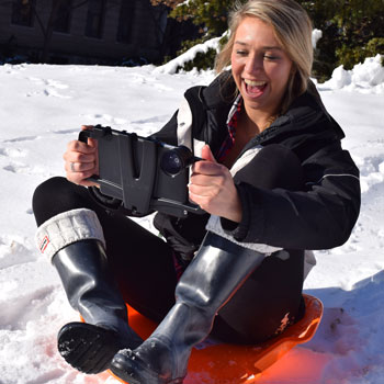 student on sled with camera