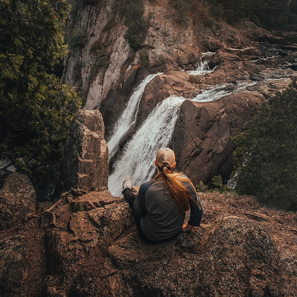 girl in hiking clothes sitting on cliff in front of waterfall